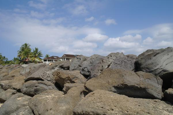 Large volcanic rocks stacked up along the edge of the beach and the civilization beyond... bringing a measure of safety when large waves break and threaten to wash over the road...
